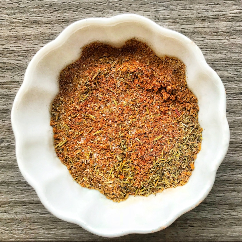 [Photo Description: creole seasoning in a round dish placed on top of a wooden board]