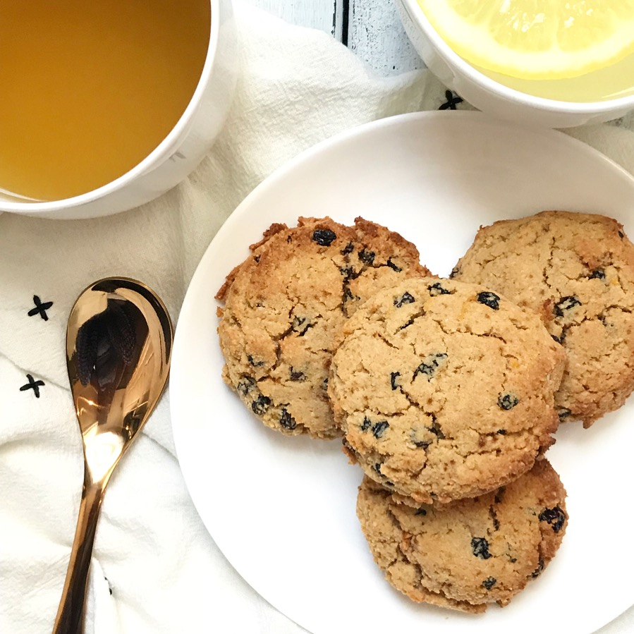 Photo Description: four Lemon Currant Gluten-Free Scones on a small round white plate, on top of a white tea towel with tiny x's stitched on it. A rose gold spoon to the left of the plate of scones accompanied by a cup of green tea in the top left corner of the photo and a cup of warm lemon water with a slice of fresh lemon in the top right corner of the photo
