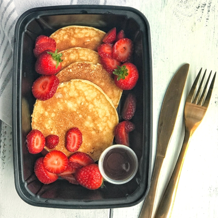 Photo Description: 4 round pancakes in a rectangle container with sliced strawberries, small round container of syrup with a knife and fork to the right of the container