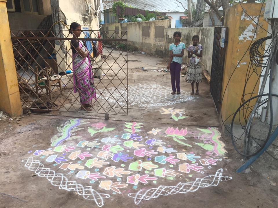 I pass by this driveway every day on the way to school. The woman on the left seems to be the gatekeeper. I'm not sure, as she doesn't speak English and I don't speak Tamil. Anyway, every day by 7:00 a.m. she draws two large and beautiful rangoli on the driveway - one in color and one in white. In school I learned that rangoli are one of many types of offerings made in the Indian culture. This par  ticular offering is a blessing for everyone in the area. The rangoli is traditionally drawn with rice flower so that the birds can eat it and also be blessed. How sweet is that? The new color powders are made with artificial ingredients and are not for the birds. This lady and her rangoli bring me such joy every day that on this particular day I decided to do something nice for her. I brought her a garland of jasmine flowers to wear in her hair. I think I'll keep up the kindness. I'll have to think of something to bring her tomorrow. Maybe a fruit.  :)