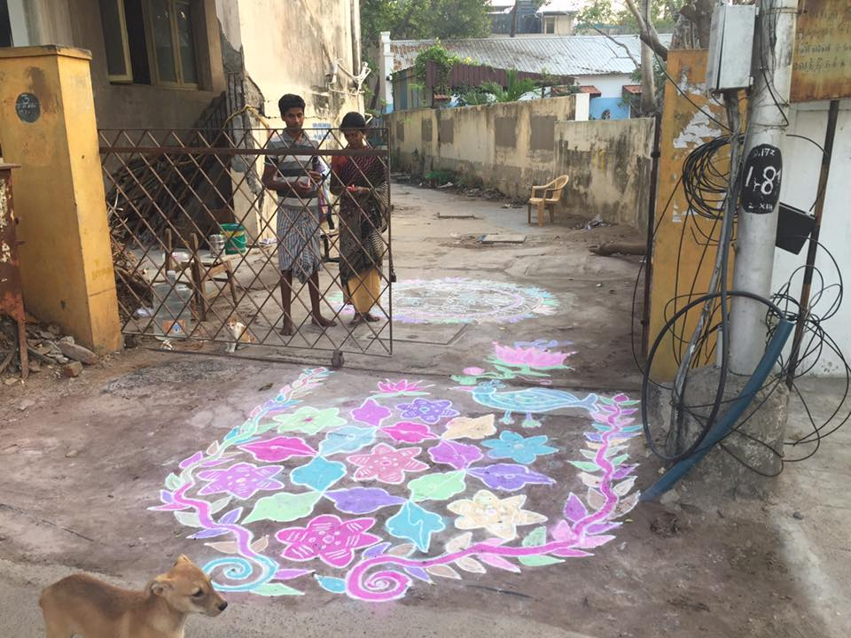 Here's my friend (I don't know her name yet as we don't speak the same language) and today's beautiful rangoli. If you recall, rangoli is another type of yajña, an offering for the well-being of the home, neighborhood, and nearby people.    I have kept up my tradition of bringing her a little gift each day, to return the happiness that she brings me with her beautiful art. Yesterday I brought her 3  tangerines (she usually has two girls with her) and today I brought her 3 candy canes I brought from Texas. Her face lights up with each little gift. It might just be the best part of my day.  Notice that this one has a pretty blue bird and a big lotus flower just inside the gate. The lotus flower symbolizes rising up out of the mud and becoming something beautiful.  I walked by again on my way home from lunch and she showed me the book she was using to plan tomorrow's rangoli.  <3