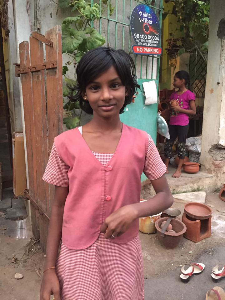 This sweet girl asked me to take her photo on my way home from school. She's wearing a school uniform. On the ground behind her you can see some terra cotta pots. The one with the gap on the front of it and the bowl on top is where a traditional Pongal food is made. They cook rice, lentils, milk, and sugar in the bowl over a fire made with wood. They intentionally let the milk overflow as a symbol of abundance. What a nice tradition!    :)