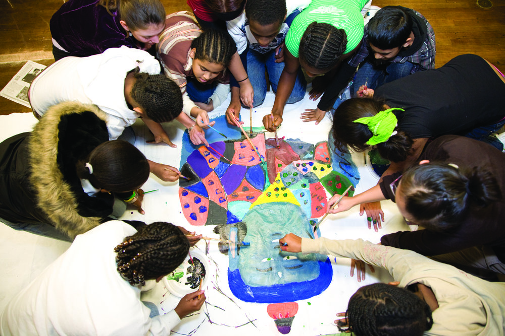 a large group of students surround a painting of the buddha that they are collaborating on.