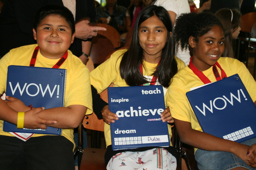 three children are sitting down and looking proud and happy by smiling at the camera.  they are all holding binders that say wow! or have the values of citizen schools written on them in large letters.