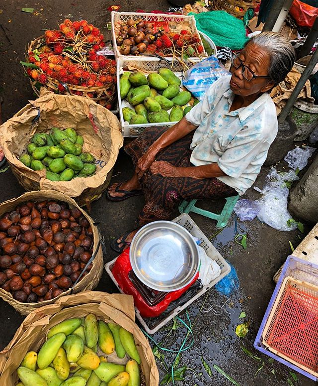 Shopping for fruits and vegetables before our cooking course in Ubud, Bali.  This local lady had a lot of character in her face.  Probably a hard life.  Rambutans, mangosteens, mangos, and more.  Www.livingfreerange.co