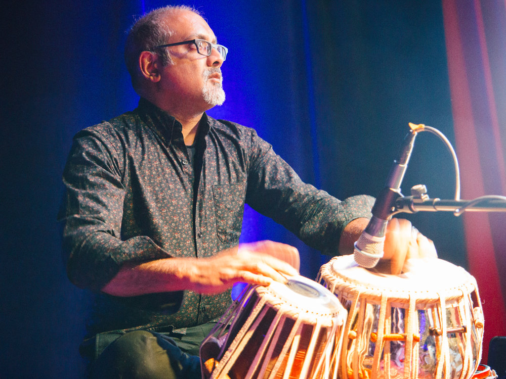 Ravi Naimpally - Ravi studied the art of tabla playing in Mumbai and Kolkata, India. Having completed extensive training with his uncle Pandit Nikhil Ghosh and later with Pandit Anindo Chatterjee, Ravi has been an active member of the Canadian world music scene for nearly 20 years. Over the past many years, Ravi has collaborated with a wide variety of artists and performed with many genres of music including Hindustani, jazz, folk, rock and world. For 12 years Ravi ledhis Indo-jazz group Tasa through several international tours and recordings that earned them an Urban Music Award. In 2011 Ravi received the Grant's Desi Achievers Award for his contribution to the South Asian community in Canada.Ravi has performed with the Miles Davis Electric Band and tours internationally with Persian/Electronic band Niyaz. As a composer and performer, he contributes to So Long Seven and Near East, two Canadian world music ensembles as both a composer and performer. Ravi is on the faculty of music at Humber College and York University.
