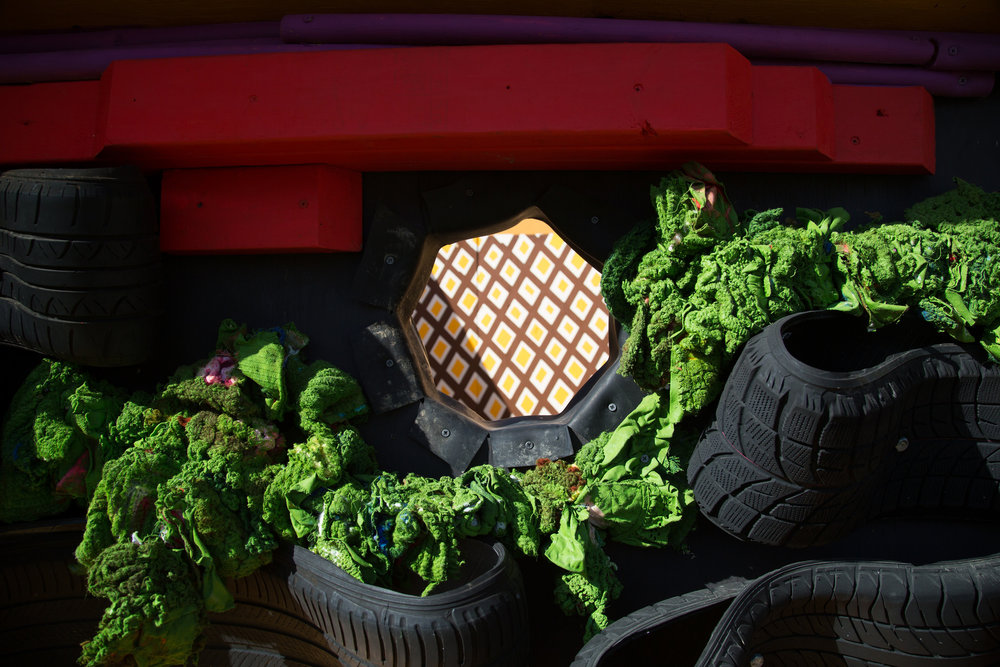 A porthole in-between the slice of plywood tomato and rag lettuce gives viewers a peek inside the burger. Photo credit: Ivette Spradlin