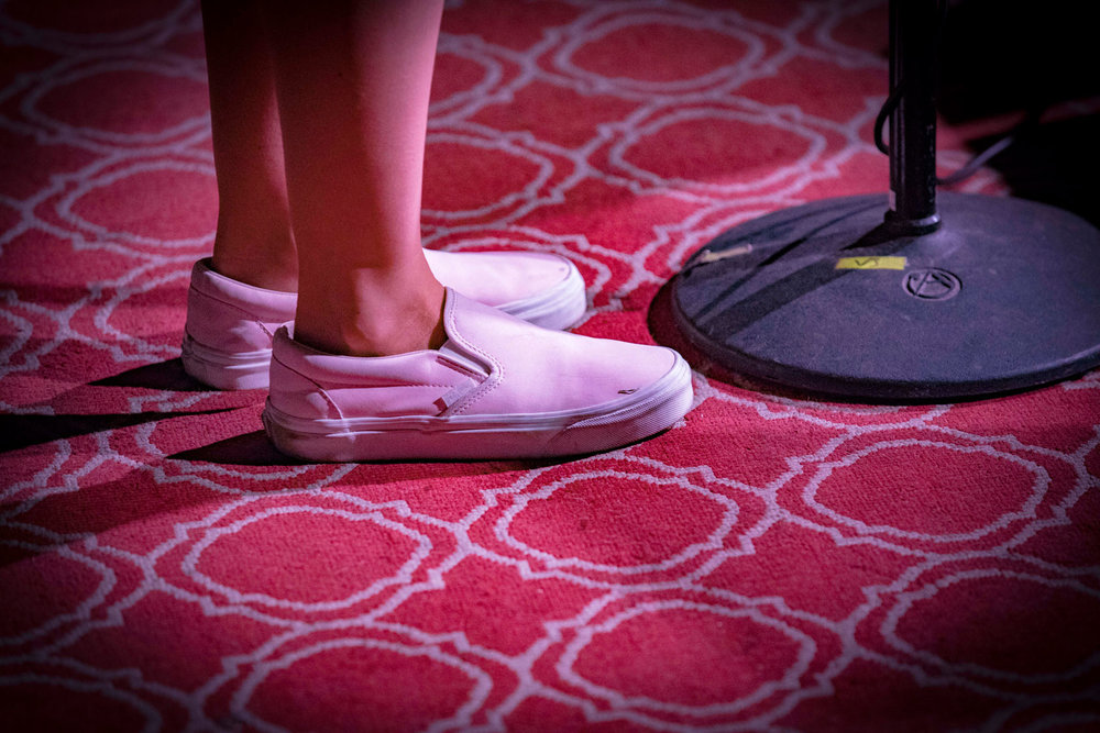 The patient feet of a storyteller await their turn at the mic. (Photo credit: Ricky Steel & The Moth)