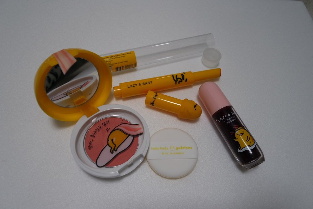 L-R: Gudetama Jelly Dough Blusher (CR01, KRW 8900), Gudetama Melting Lip Button (OR02, KRW 10 900), Gudetama All Night Tint (#1 Red Queen, 5ml, KRW 5900)