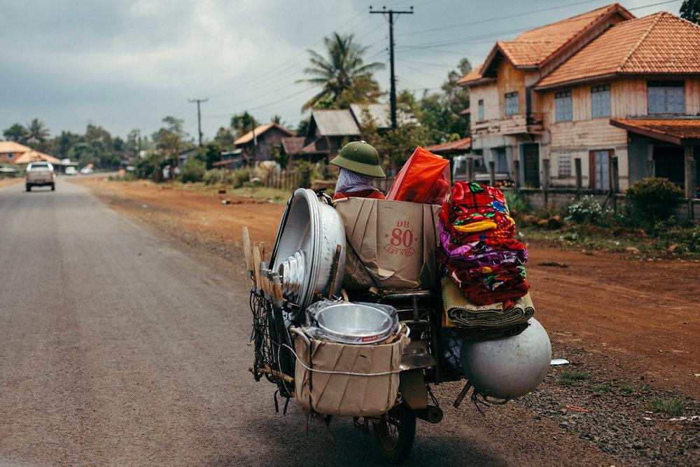laos pakse motorbike overpacked lady handzaround