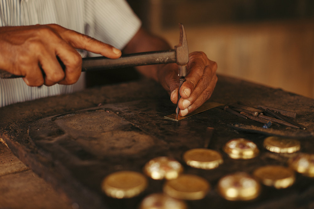 The local craftsmen working on the keychain for Hanna