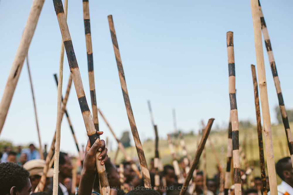 Local boys and men holding up their traditional weapons