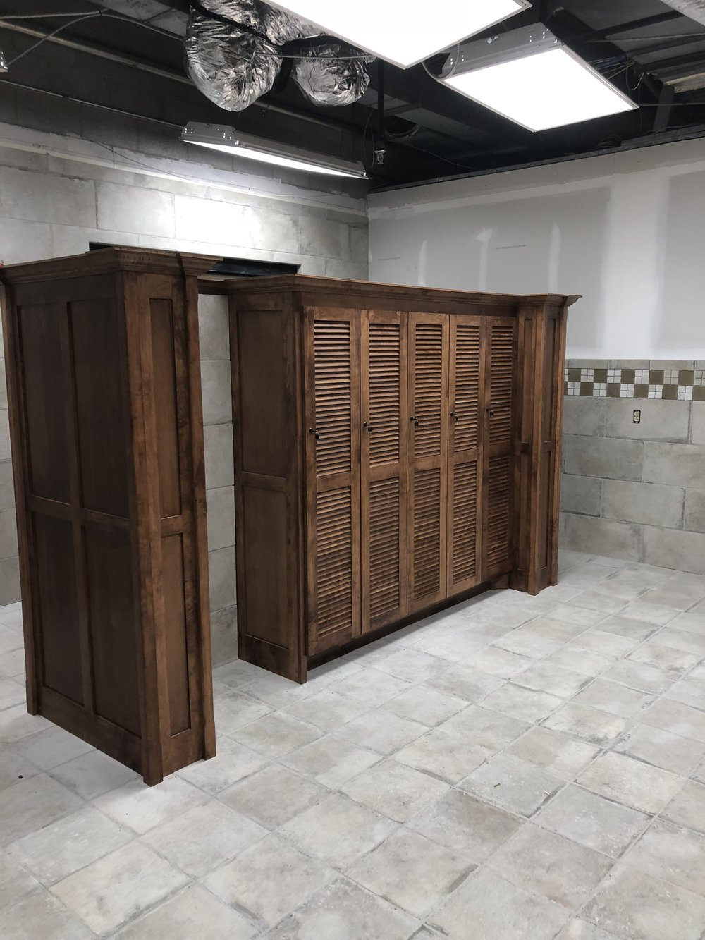 Going with highly figured maple, decorative crown molding, and true louvered doors really sets this commercial locker room apart.