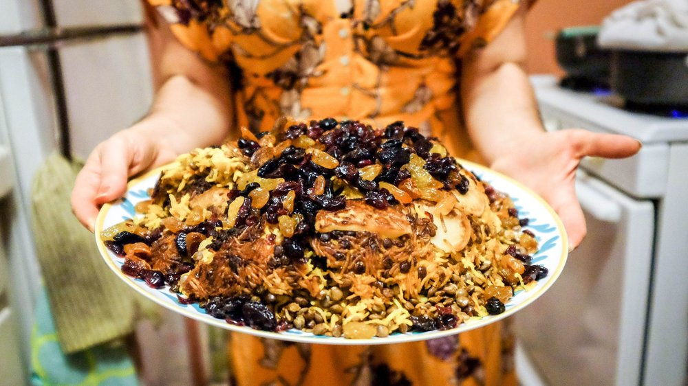"Closeup of me holding the Adas Polo (Lentil Rice with raisins + cranberries). This rice also has a potato ""tahdig"" which is the crusty rice developed at bottom of the pot. Photo: Meghan McCarron for  la.eater.com"