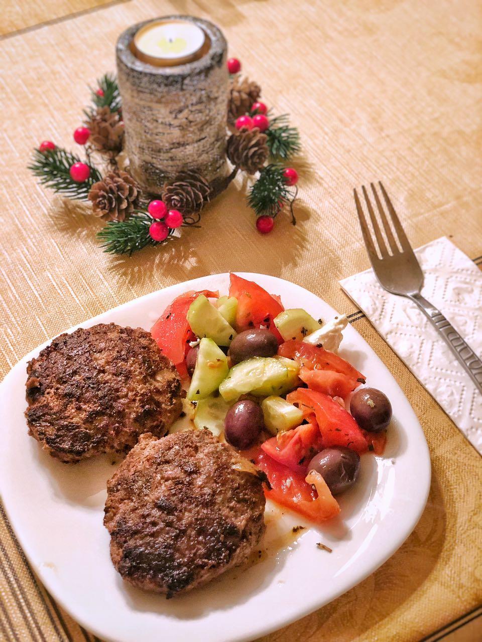 Конски кюфтета със салата от домати, краставици, авокадо, маслини и лук.