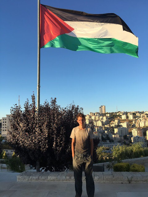 Me under a Palestinian flag at the Mahmoud Darwish Museum in Ramallah.