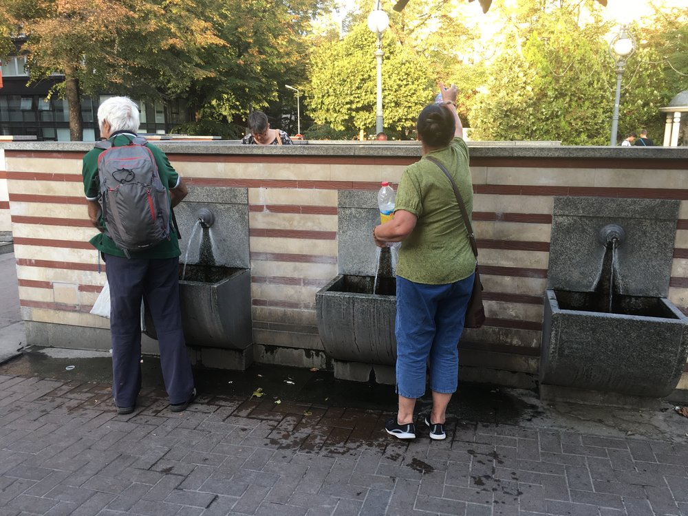 In the heart of Sofia there are constantly flowing taps where you will see locals filling up bottles of the hot mineral water, free of charge.  I went on a Free Sofia Walking Tour today and the guide said people believe ingesting the water also has health benefits, like improving heart disease or stomach problems, but mostly they just fill their gallons each week because it's free!