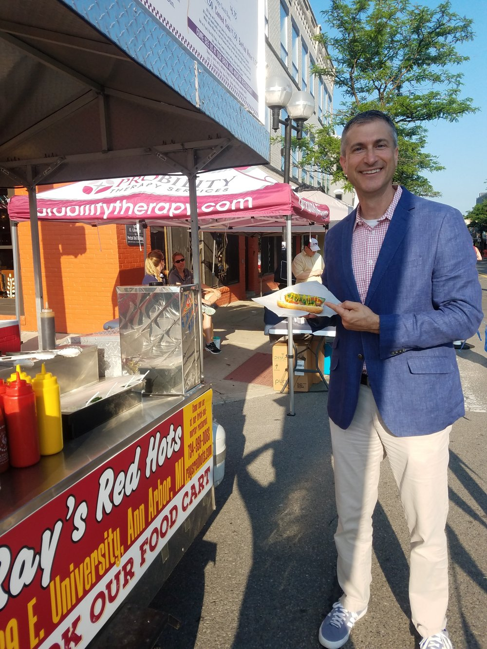 Ann Arbor Mayor Chris Taylor enjoys a Chicago Dog (no onions!) at the Fourth of July Parade 2018.