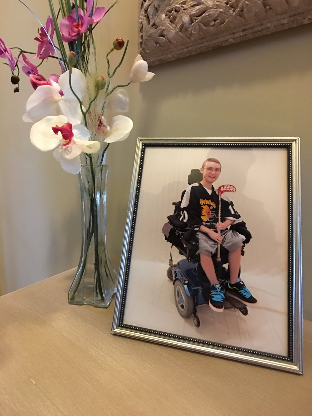 In their foyer, a photo of son, Justin.  He was an intelligent, vigrant young man who loved playing adaptive floor hockey, video games and loved to pursue girls.
