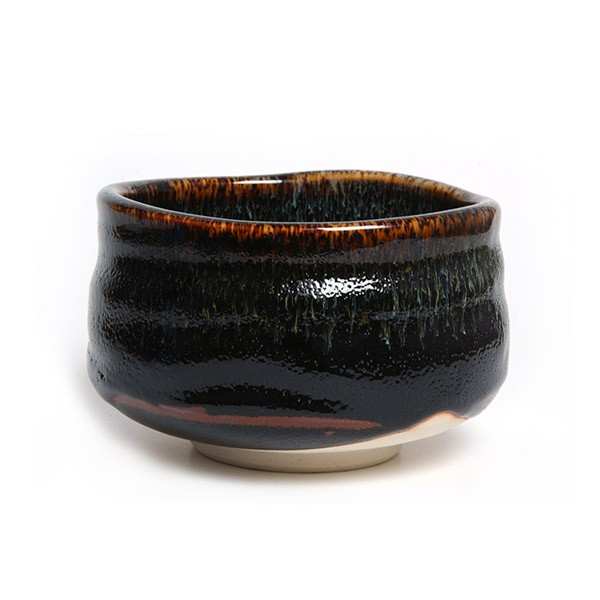 """Vores japanske ceremoni skål er af typen RAKU og betegnes som den """"originale"""" skål type - den er sort og med røde/brune nuancer.  Vores ceremoni skåle er håndlavede af en af japans dygtigste pottemager og hans værksted ligger i det centrale Kyoto."""