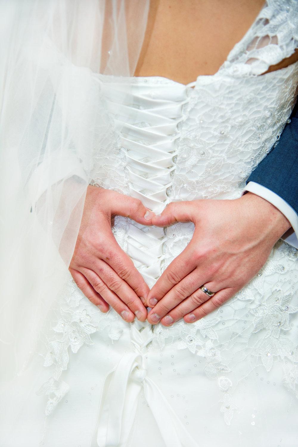 Groom making hand heart on wedding dress