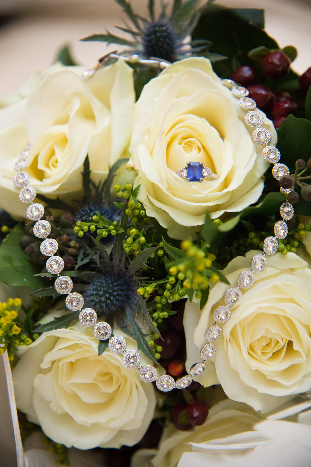 Wedding ring and bridal necklace on bouquet