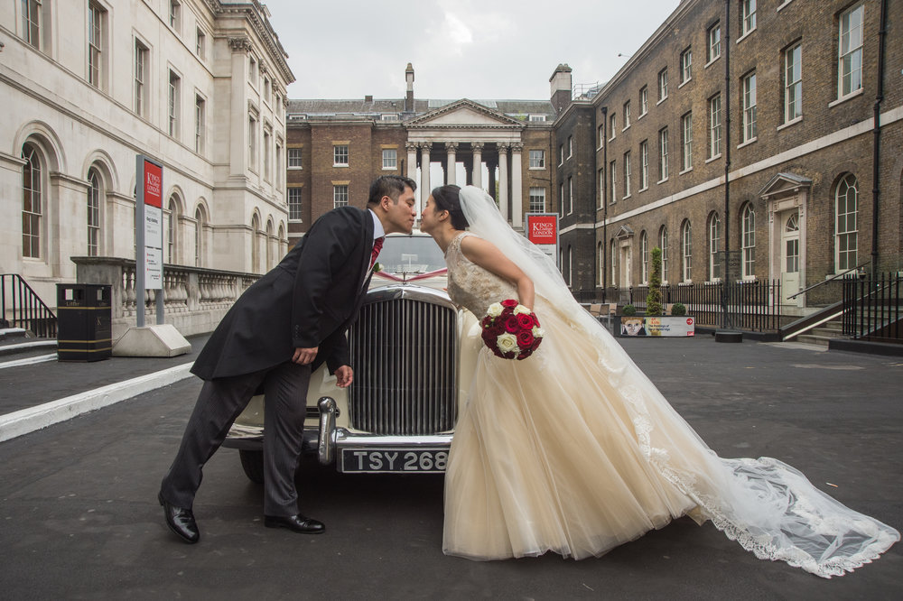 Bride and Groom with wedding car in the Courtyard of Kings College London