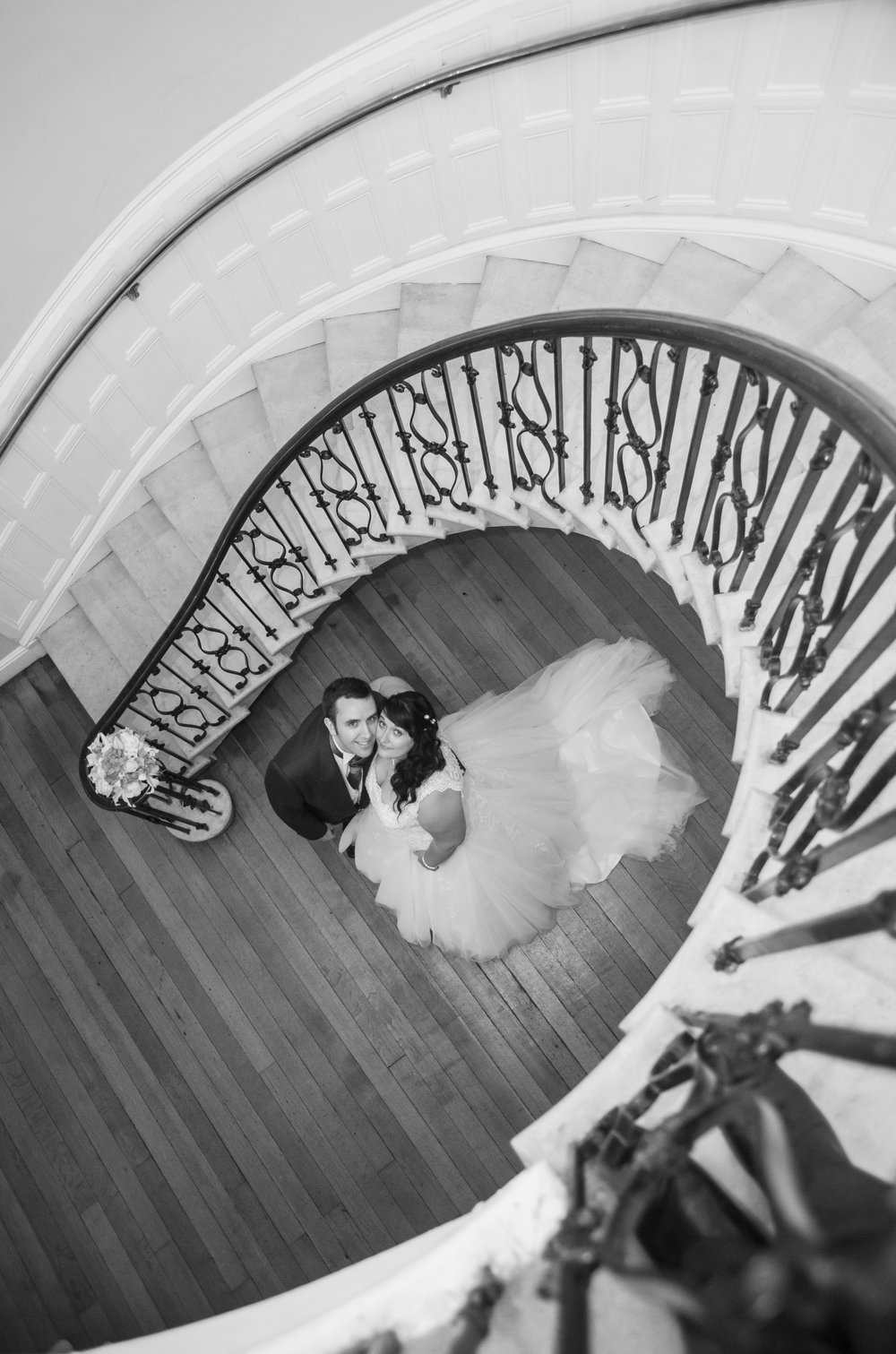 Bride and Groom under staircase Eastington Park Gloucestershire
