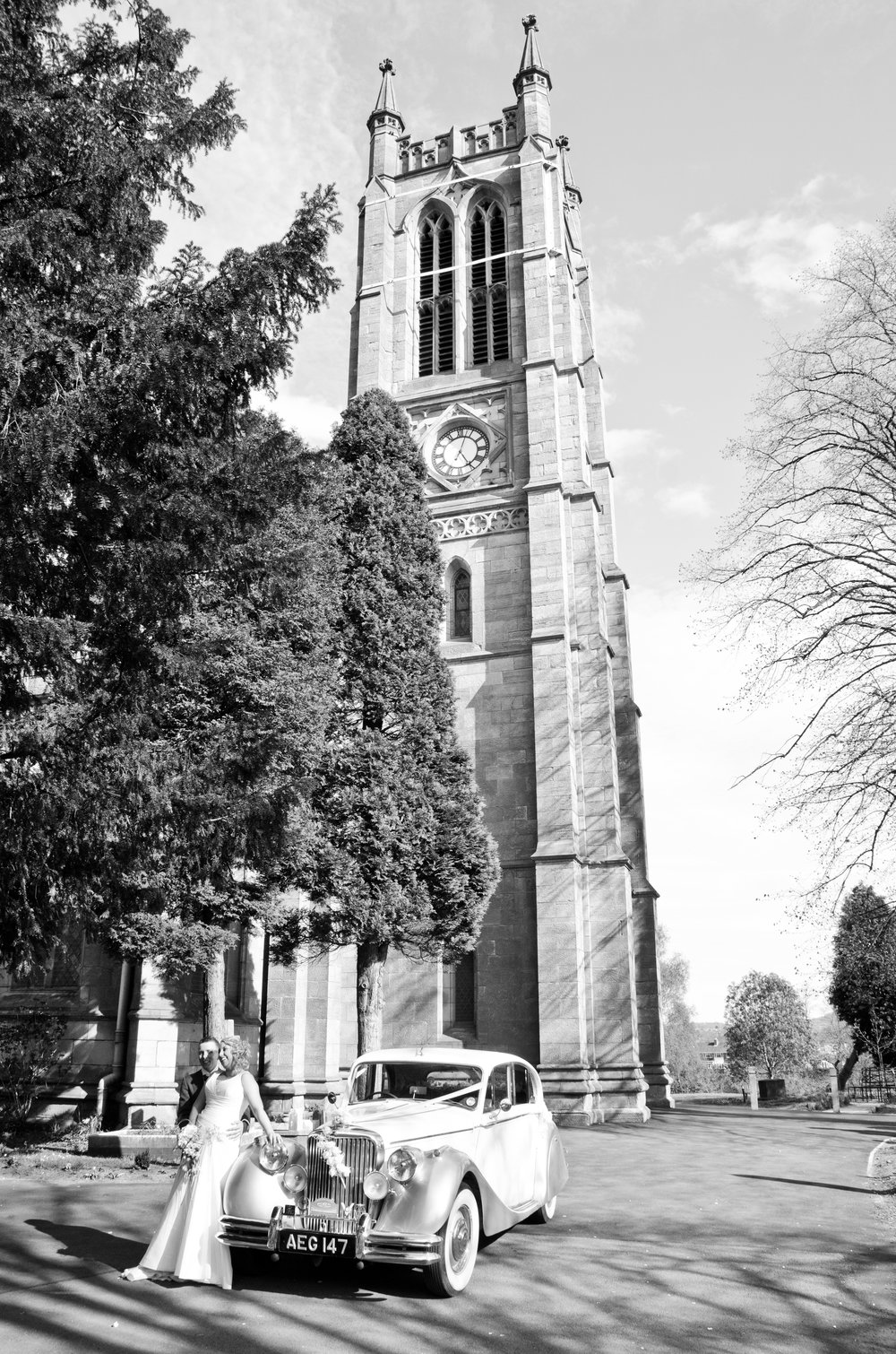 Bride and Groom by wedding car Holy Trinity Church Wordsley Stourbridge