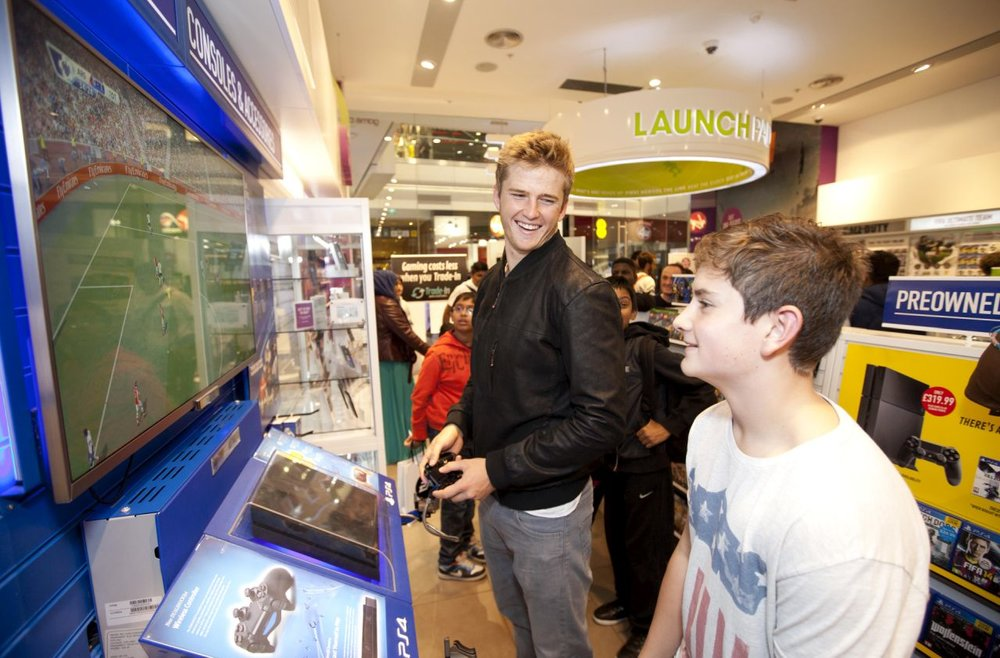 EDITORIAL USE ONLY Tottenham Hotspur's Eric Dier plays a game of FIFA 15  Joshua Simpkins at the GAME store in Westfield Stratford City in London, ahead of the store�s midnight launch of FIFA 15. PRESS ASSOCIATION Photo. Picture date: Thursday September 25, 2014. Photo credit should read: David Parry/PA Wire
