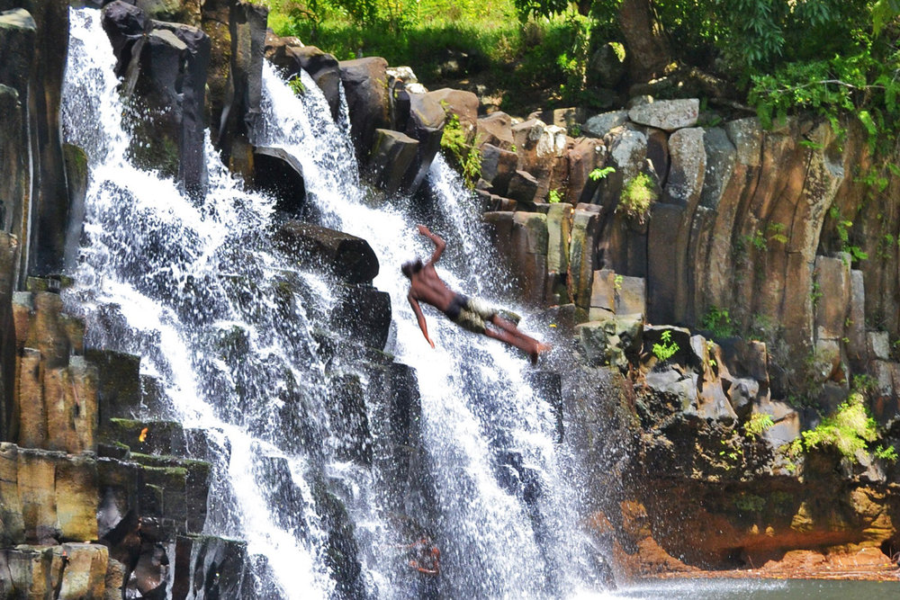 Young man jumping from the waterfall