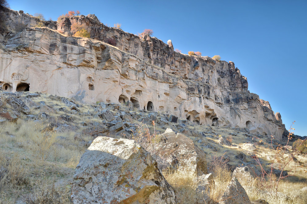 Cave dwellings in the wall of the cliff, similar to  Vardzia in Georgia