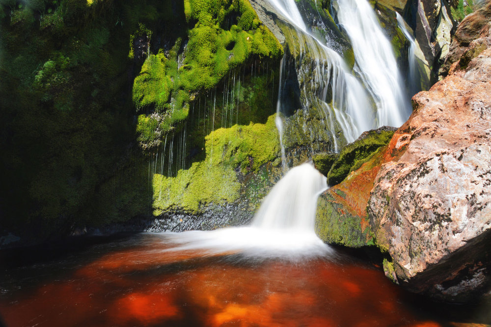 A pool of clear, red water at the bottom of the waterfall