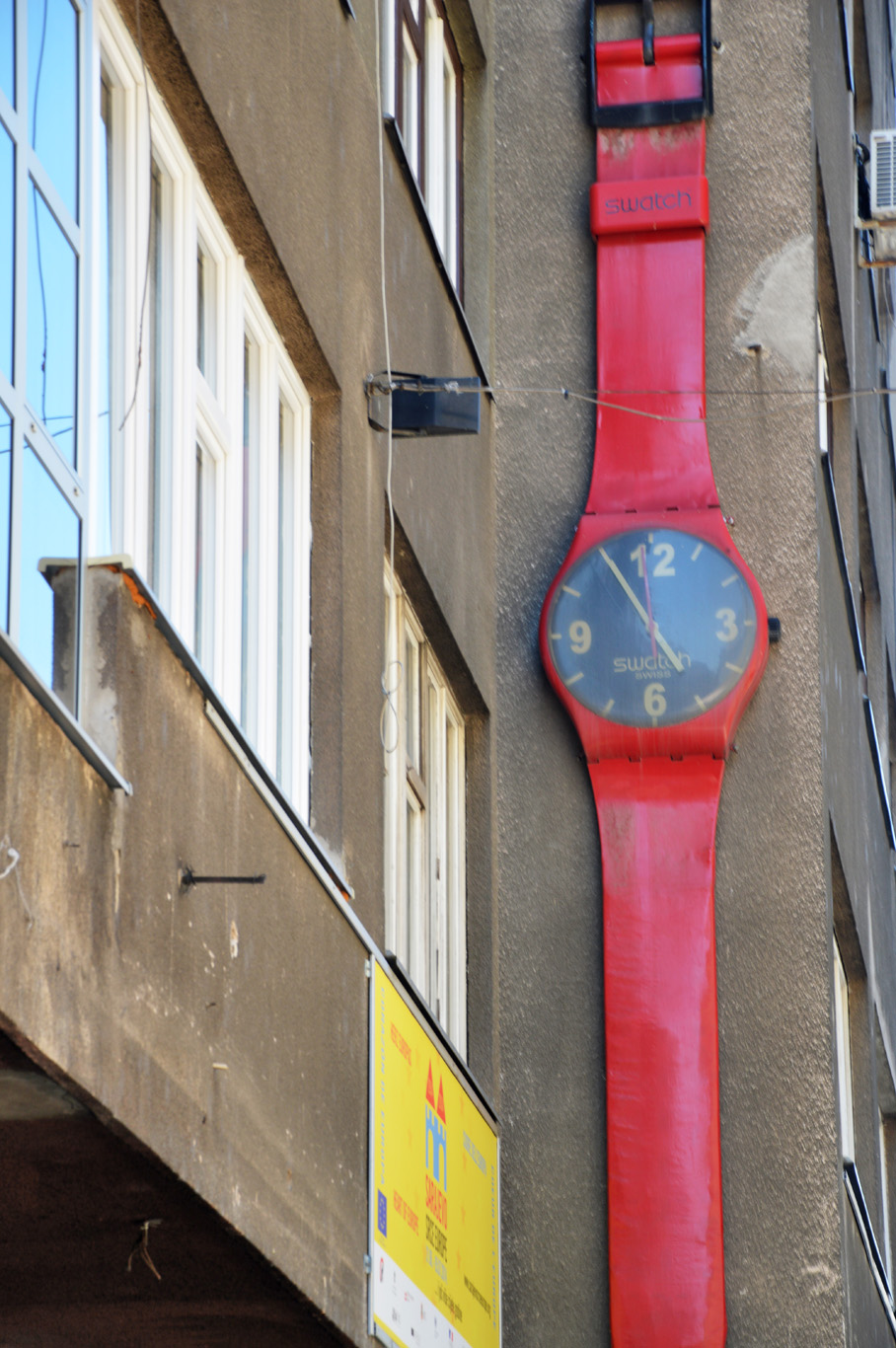 A watch on the wall of one of the buildings