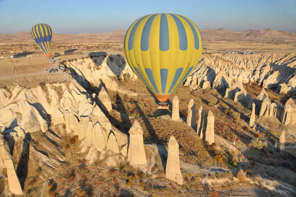 Balloons flying in between funnily shaped rock pillars