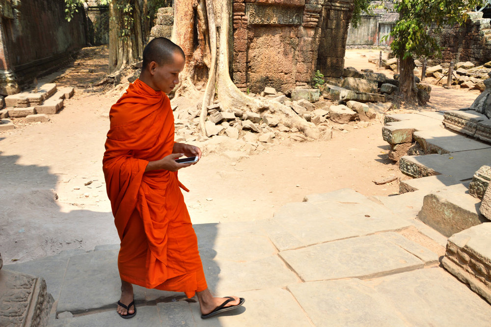 Tradition and modernity - a monk with a smartphone at Ta Phrom