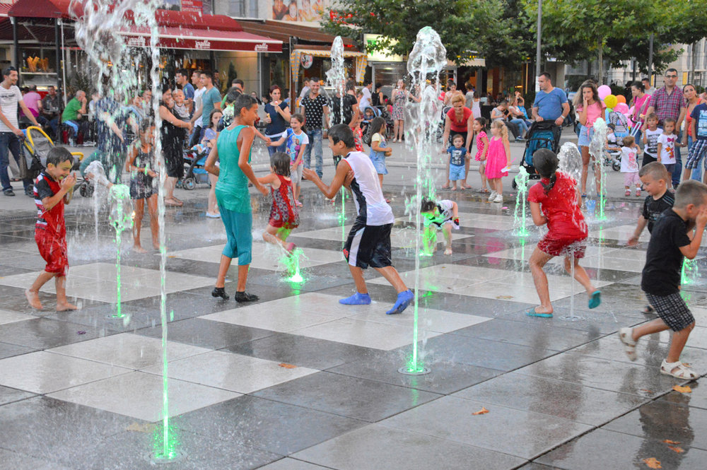 Children cool themselves at the fountains in Mother Teresa Boulevard