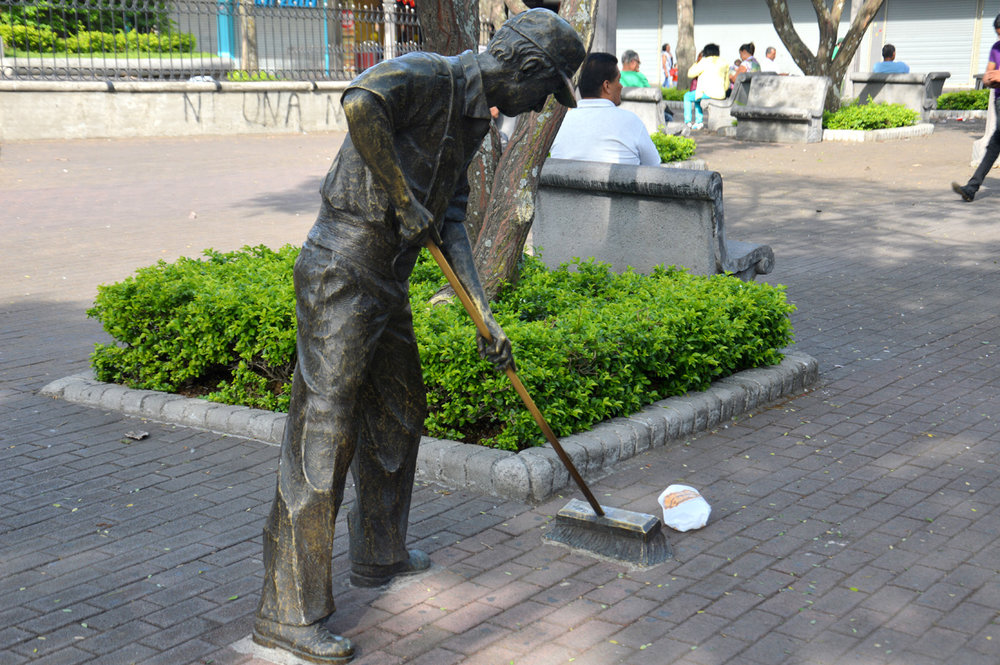 Statue of a street cleaner and a piece of trash