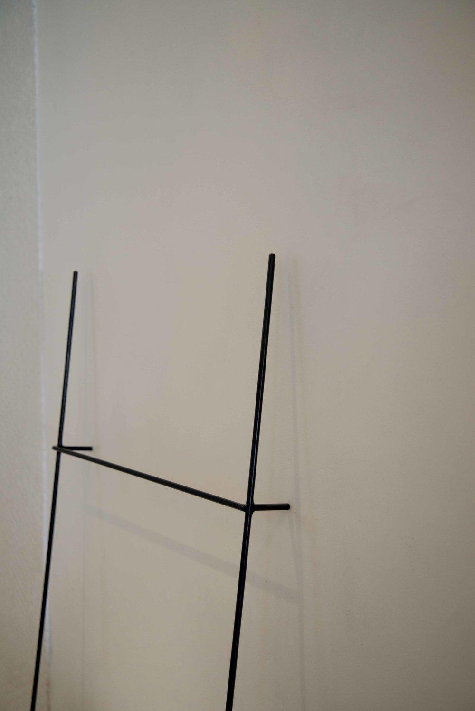 Matt black steel rod standing towel rail.