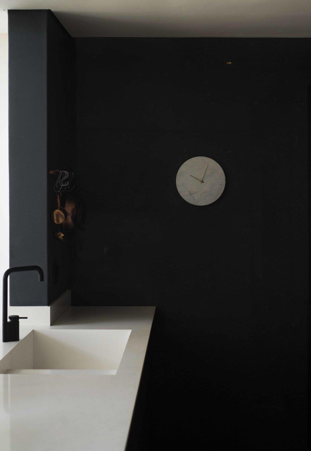 marble clock and dark wall panel