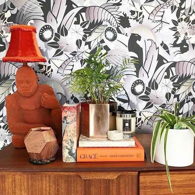 This is Jade from  Numberfiveinteriors  home.This monochrome wallpaper looks so good as a backdrop for a cluster of orange gold and cream objects. Using the same or similar colours is a great way to cluster objects to create maximum impact.