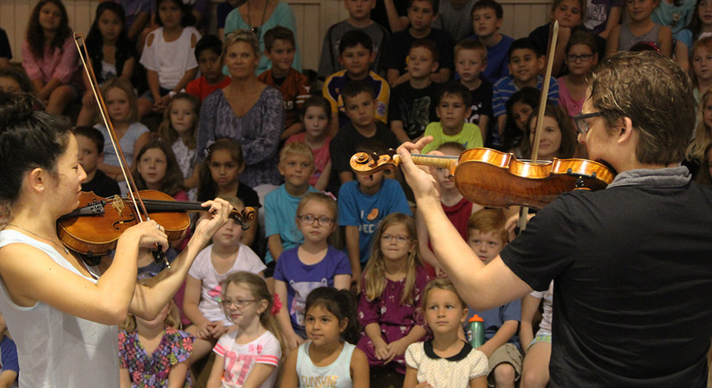 Violinists Rachel Shapiro and Nicholas Tavani, members of the Aeolus Quartet, perform and teach children at Sacred Heart Catholic School in La Grange.