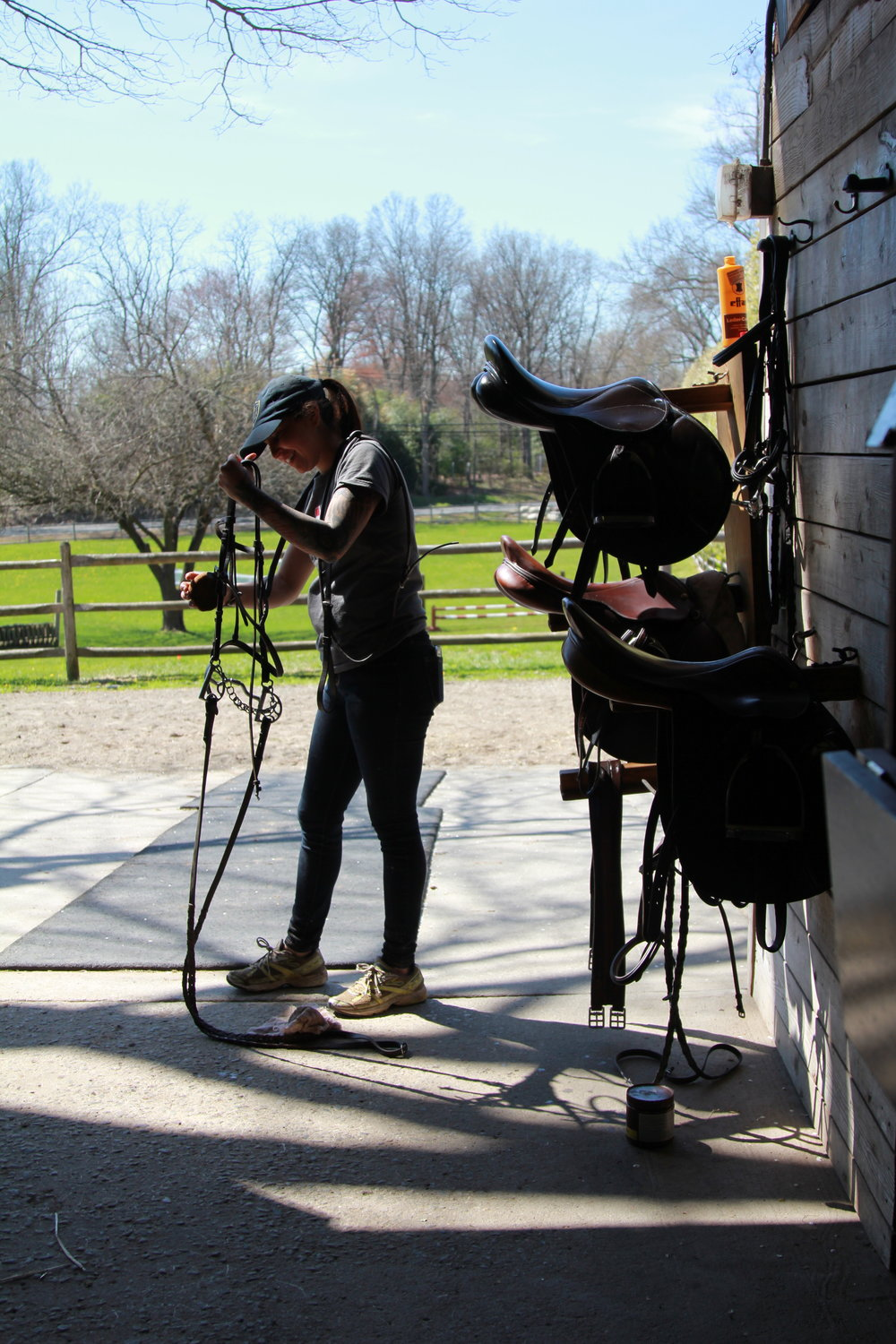 Vanessa cleaning tack after a horseback ride
