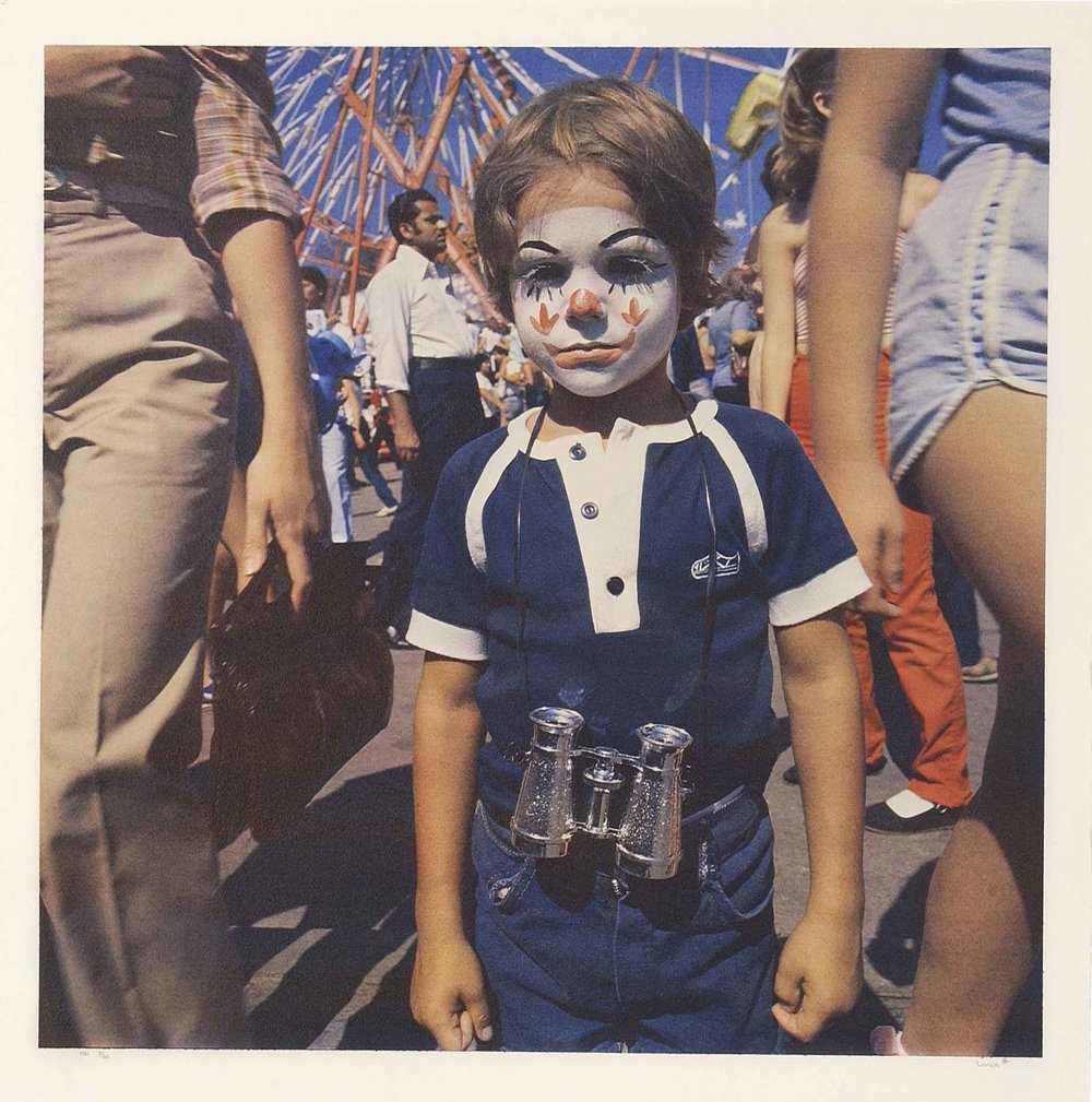 Stephen Livick: Midway    Woodstock Art Gallery   Stephen Livick's photographs examine how the carnival, traditionally considered to be a site of pleasure and amusement, can double as a site of melancholy. The tension between the faces of the individuals and their entertaining surroundings, specifically in the coloured photographs, are precisely what makes these photographs so engaging. Behind the strained smiles, face paint and clown masks lies a profound dissatisfaction that contradicts the very character of the carnival itself.