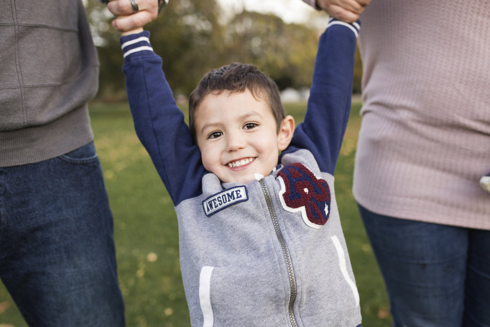 Rochester Family Photographer, How to get your family excited for photos, little boy happily swinging with his mom and dad