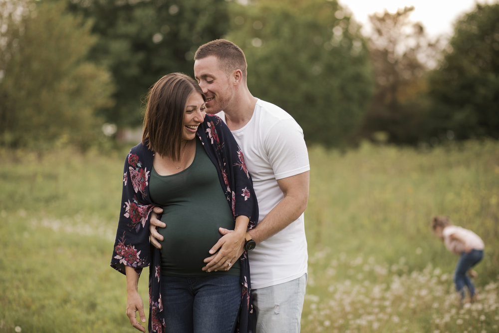 Maternity Photographer Rochester NY, Mom and Dad to be laughing  together while daughter plays in the field behind