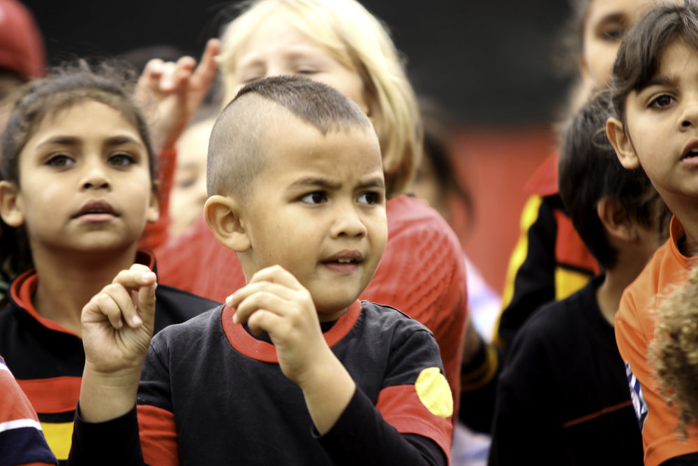 Koori kids showing their pride in culture for the Aboriginal flag, red, black and yellow
