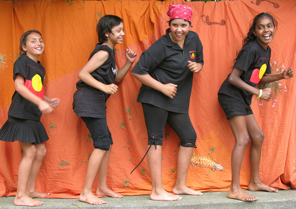 Aboriginal girls singing with lAboriginal anguage words from Wiradjuri language dancing wearing Aboriginal flag T Shirts, red, black and yellow