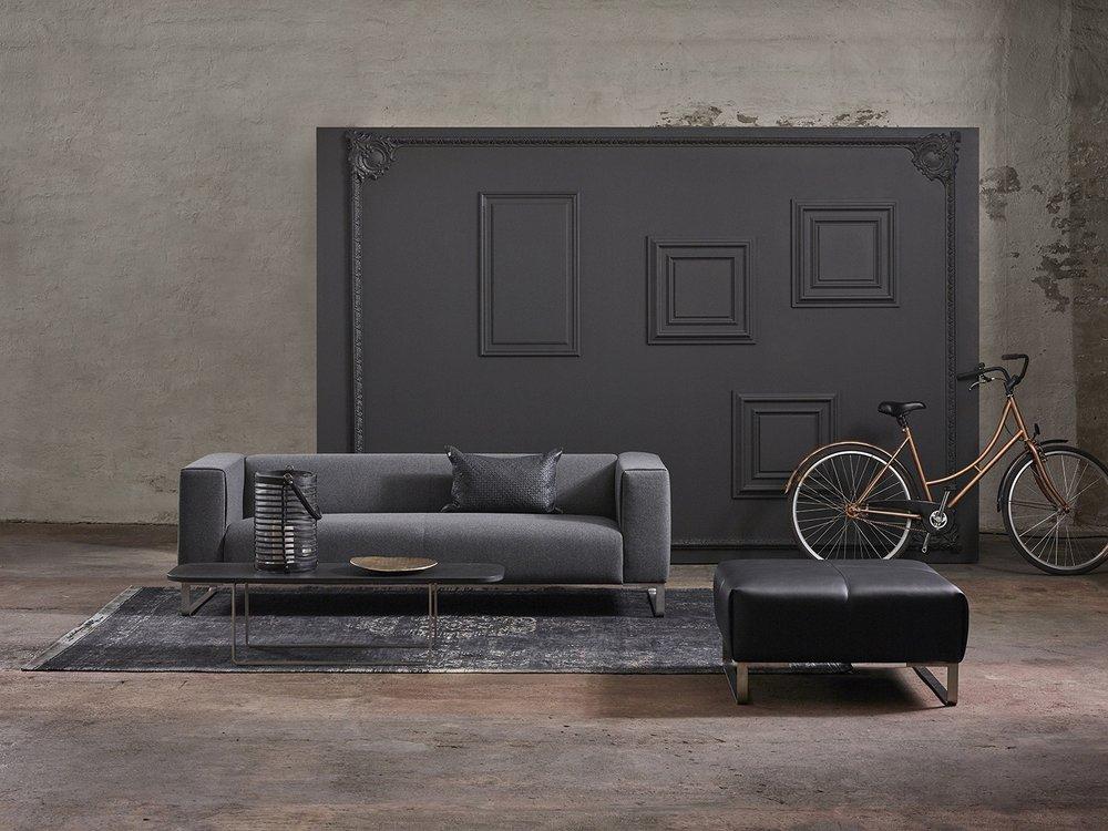 Fender 3-seter i Wooly antrazit tekstil og ben i rustfritt stål. Fender pall i hud Vogue black og Fender avlangt bord i sort granitt og rustfritt stål.