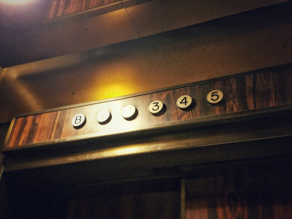 """Inside of the elevator at 60 Centre Street, showing the floor indicator lights from """"B"""" (basement) through 5."""